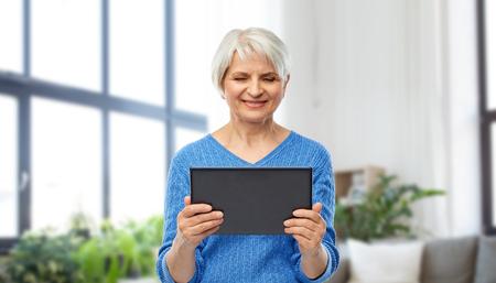 senior woman using tablet computer at home
