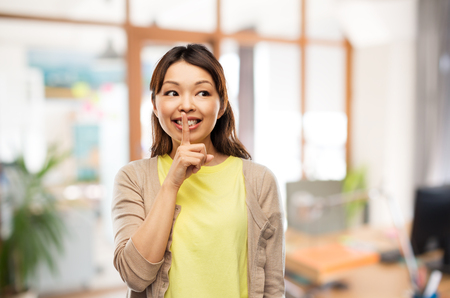 happy asian woman with finger on lips