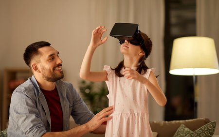 father and daughter in vr glasses playing at home Stock Photo