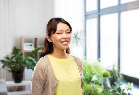 happy asian woman over home background Stock Photo