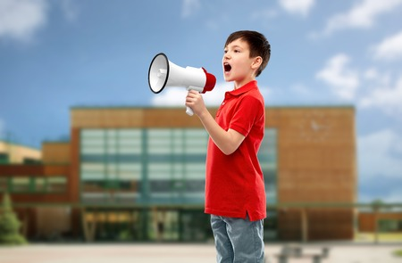 little boy in red polo shouting to megaphone Stock Photo