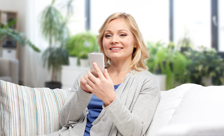 smiling woman with smartphone texting at home