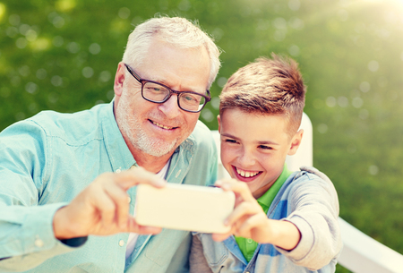 old man and boy taking selfie by smartphone Stock Photo
