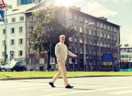 senior man walking along city crosswalk
