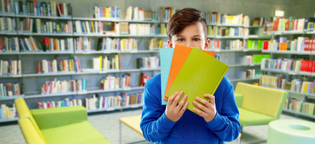 shy student boy hiding behind books at library