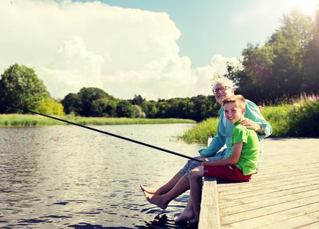 grandfather and grandson fishing on river berth Фото со стока