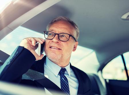 homme d'affaires senior appelant sur smartphone en voiture