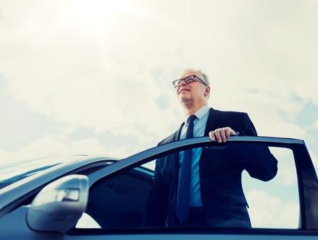 senior businessman getting into car Imagens