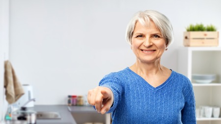 senior woman pointing finger to you at kitchen