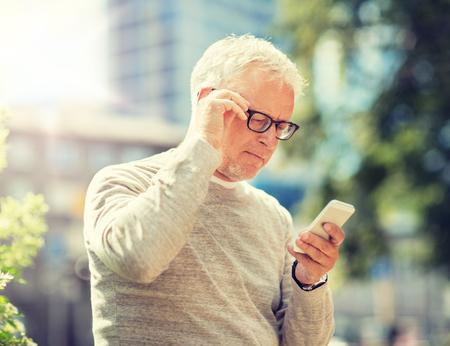 starszy mężczyzna wysyła wiadomość SMS na smartfonie w mieście Zdjęcie Seryjne
