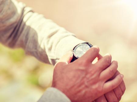 senior man checking time on wristwatch outdoors