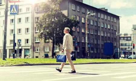 senior man with shopping bags walking on crosswalk Zdjęcie Seryjne - 124309718