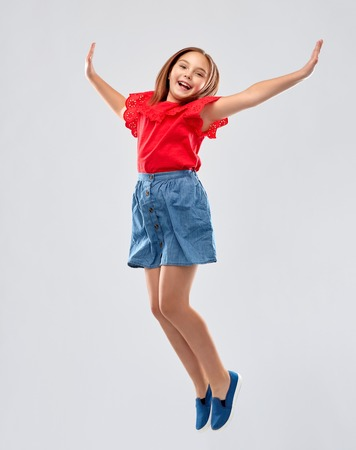 happy smiling girl in red shirt and skirt jumping Stock Photo