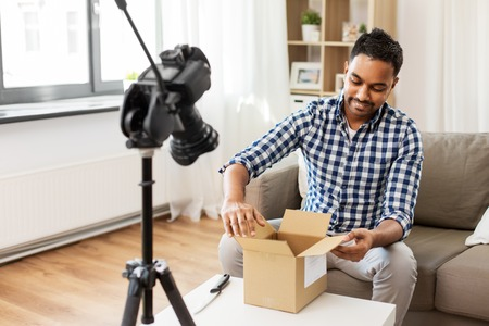 male video blogger opening parcel box at home Imagens