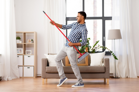 man with broom cleaning and having fun at home Banco de Imagens