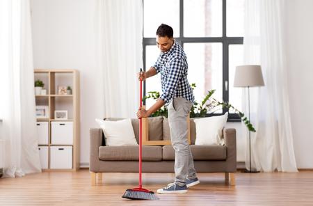 mężczyzna z miotłą czyści podłogę w domu