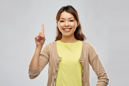 happy asian woman pointing finger up 版權商用圖片