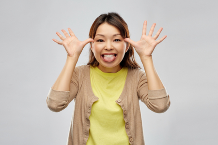 funny asian woman making silly faces 版權商用圖片