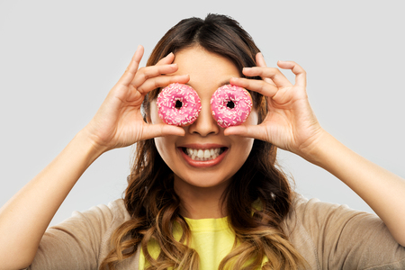 happy asian woman with eyes of donuts