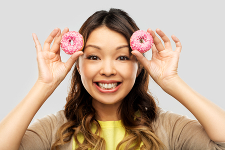 happy asian woman with donuts