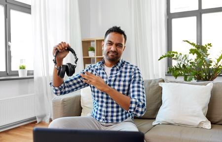männlicher Blogger mit Kopfhörern Videoblogging zu Hause Standard-Bild