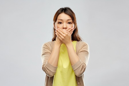 scared asian woman over grey background