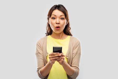 sorprendida, mujer asiática, utilizar, smartphone
