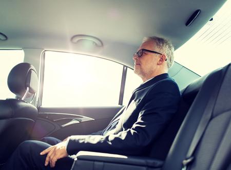 leitender Geschäftsmann, der auf dem Rücksitz des Autos fährt