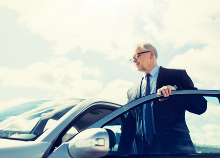 senior businessman getting into car