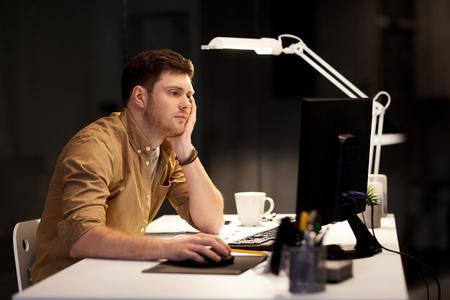 müder oder gelangweilter Mann, der spät im Büro arbeitet