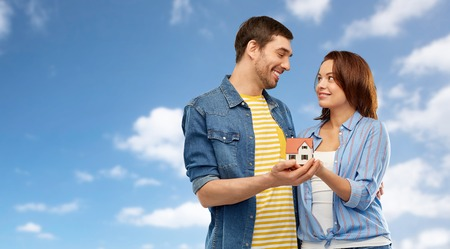 smiling couple holding house model