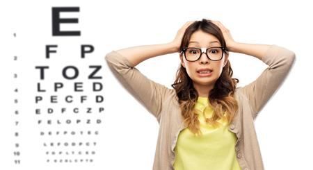 gestresste vrouw met bril over oogtestkaart Stockfoto