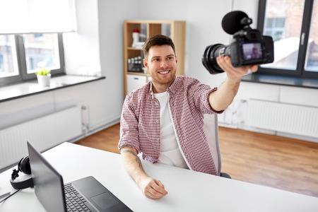 male blogger with camera videoblogging at office Banco de Imagens