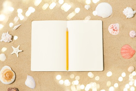 notebook with pencil and seashells on beach sand