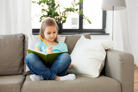 little girl with diary sitting on sofa at home