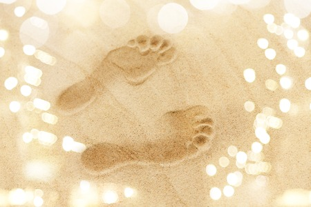 footprints in sand on summer beach