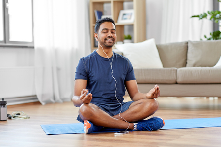 Hombre indio meditando en posición de loto en casa