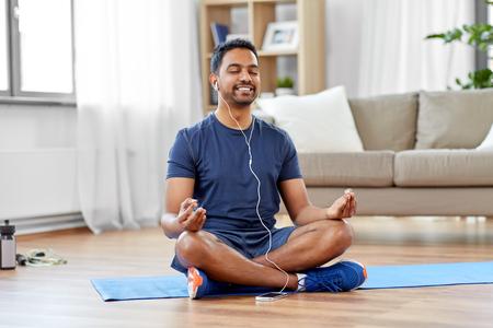 indian man meditating in lotus pose at home