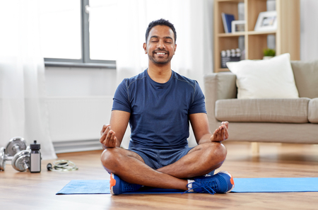 indian man meditating in lotus pose at home