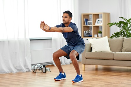indian man exercising and doing squats at home