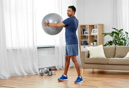 indian man exercising with fitness ball at home 写真素材