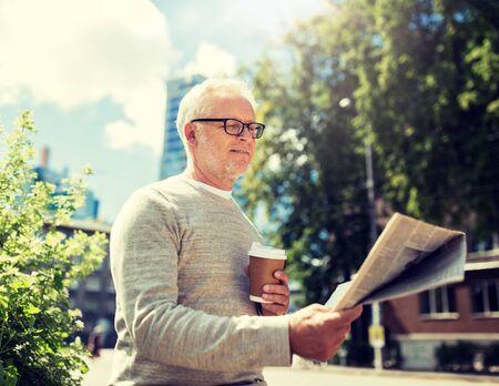 senior man reading newspaper and drinking coffee