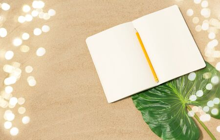 notebook with pencil and leaf on beach sand