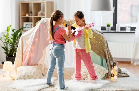 niñas con guitarra y micrófono tocando en casa