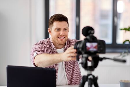 male video blogger adjusting camera at home office
