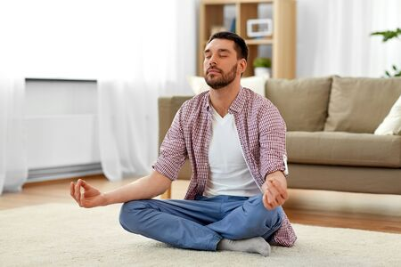 man meditating in lotus pose at home