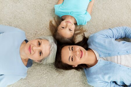 mother, daughter and grandmother lying on floor