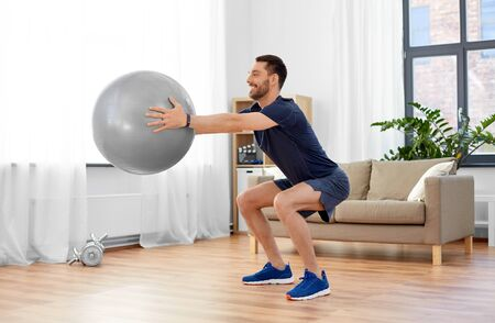 man exercising and doing squats with ball at home