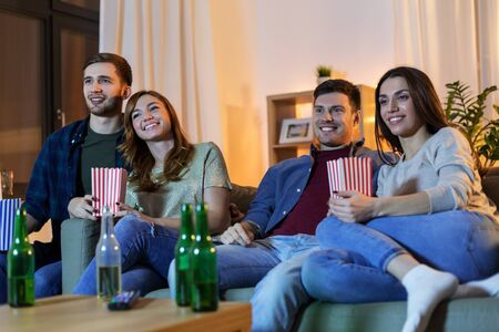 friends with beer and popcorn watching tv at home Imagens - 124455340