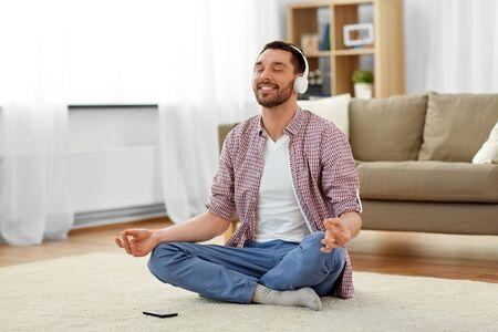 mężczyzna w słuchawkach medytujący słuchając muzyki